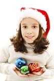 Menina no chapéu de Santa que guarda a decoração do Natal nas mãos imagens de stock royalty free