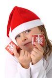 A menina no chapéu de Santa que prende pouco apresenta isolado imagem de stock