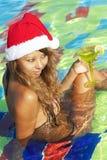 Menina no chapéu de Santa que senta-se na piscina Imagens de Stock