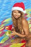 Menina no chapéu de Santa que senta-se na piscina Imagens de Stock Royalty Free
