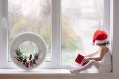 Menina no chapéu de Santa que senta-se pela janela com presentes e Cristo Imagem de Stock Royalty Free