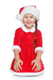 A menina no chapéu de Santa senta-se em um fundo branco Imagens de Stock Royalty Free
