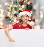 Menina no chapéu do ajudante de Santa com placa branca vazia Foto de Stock