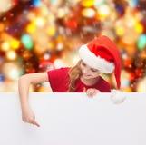 Menina no chapéu do ajudante de Santa com placa branca vazia Fotografia de Stock