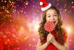 Menina no chapéu do ` s de Santa com os doces no fundo das luzes Imagens de Stock