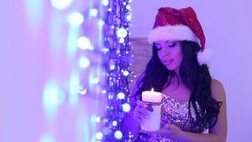 A menina no chapéu do ` s de Santa com uma vela no Natal video estoque