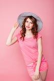 A menina no chapéu em um pinup cor-de-rosa do fundo Fotografia de Stock Royalty Free