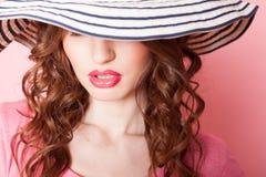 A menina no chapéu em um pinup cor-de-rosa do fundo Fotos de Stock Royalty Free