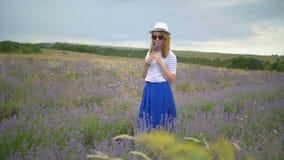 A menina no chapéu está andando em um campo da alfazema video estoque