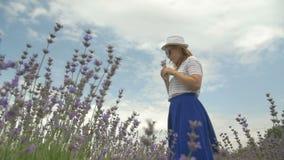 A menina no chapéu está andando em um campo da alfazema filme