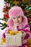 Menina no chapéu forrado a pele cor-de-rosa que guarda a árvore inferior atual de Chritmas Foto de Stock Royalty Free