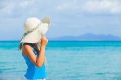 A menina no chapéu grande relaxa o fundo do oceano Imagem de Stock Royalty Free