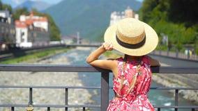 Menina no chapéu na terraplenagem de um rio da montanha em uma cidade europeia video estoque