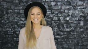 Menina no chapéu negro e na camisa cinzenta que levantam positivamente contra a parede da textura filme