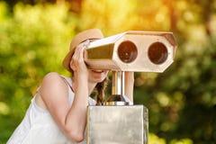 A menina no chapéu olha nos binóculos grandes Verde no fundo Front View Fotografia de Stock