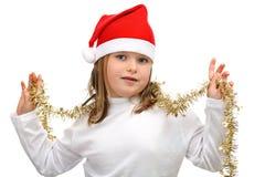 Menina no chapéu vermelho de Santa com as correntes douradas isoladas Foto de Stock