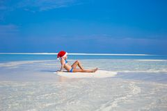 Menina no chapéu de Santa na praia durante Imagens de Stock Royalty Free