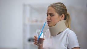Menina no colar cervical da espuma que tenta beber a água de vidro com tentativa pobre da palha vídeos de arquivo