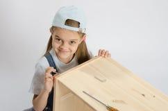 Menina no coletor da imagem do parafuso da volta da mobília Imagem de Stock