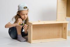 Menina no coletor dos macacões da mobília que faz a caixa no armário Imagem de Stock Royalty Free