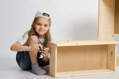A menina no coletor dos macacões recolhe a gaveta da mobília do armário Imagens de Stock Royalty Free