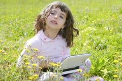 Menina no computador portátil do prado do jardim fotografia de stock
