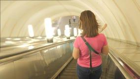 Menina no conceito subterrâneo do metro do metro Os povos estão na escada rolante no metro ou no metro, o conceito de vídeos de arquivo