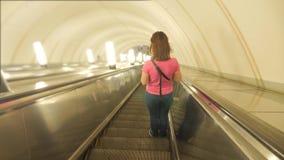 Menina no conceito subterrâneo do metro do metro Os povos estão na escada rolante no metro ou no metro, o conceito de filme