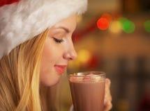 Menina no copo bebendo do chapéu de Santa do chocolate Foto de Stock