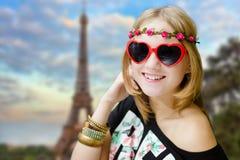 A menina no coração deu forma a óculos de sol em Eiffel borrado Imagem de Stock