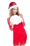 Menina no crescimento completo em um chapéu do Natal que guarda bandeiras nas FO Fotos de Stock
