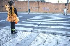 Menina no cruzamento de zebra em trajes do Dia das Bruxas para o chil Fotografia de Stock