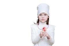 A menina no doutor veste-se com um estetoscópio e uma cruz vermelha no chapéu Fotografia de Stock Royalty Free