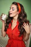 A menina no estilo retro bebe o chá Imagens de Stock Royalty Free