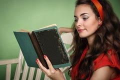 Menina no estilo retro com emoções que lê um livro Fotos de Stock