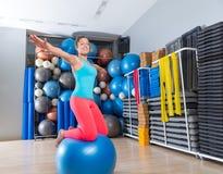 Menina no exercício suíço da broca do equilíbrio do joelho da bola do gym Fotografia de Stock Royalty Free