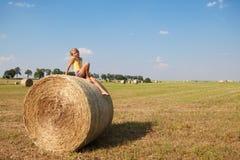 Menina no feno no campo do outono Imagem de Stock Royalty Free