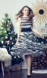 Menina no fundo da árvore de Natal Foto de Stock