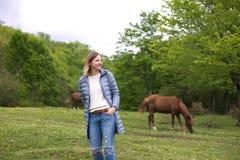 Menina no fundo de pastar cavalos fotografia de stock