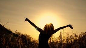 Menina no fundo de suportes ensolarados brilhantes e de acenar de um por do sol suas mãos entre as flores no campo entre filme