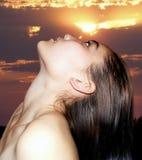 Menina no fundo do sol do pôr do sol Fotografia de Stock