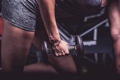 A menina no gym agacha-se com um barbell, em um uniforme bonito dos esportes, contra um fundo escuro Imagens de Stock