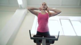 A menina no gym executa um exercício nos músculos da parte traseira Hiperextensão video estoque