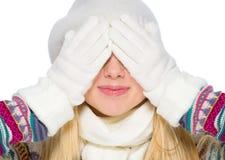 A menina no inverno veste os olhos da coberta com mãos Imagem de Stock