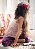 Menina no janela-peitoril que olha para fora a janela imagens de stock