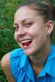 A menina no jardim com as bagas das framboesas em sua boca Imagens de Stock Royalty Free