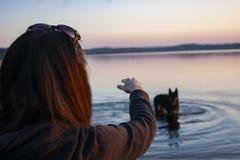A menina no lago que joga com um cão imagens de stock