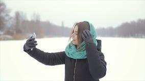 A menina no lenço verde e em um revestimento preto faz o selfie vídeos de arquivo
