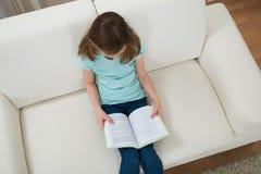 Menina no livro de leitura do sofá Imagem de Stock