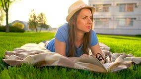 Menina no livro de leitura dos vidros que encontra-se para baixo em uma cobertura no parque no por do sol filme